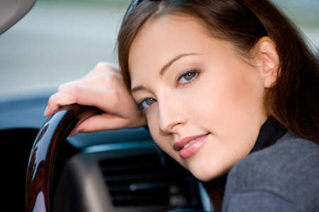 brunets: Portrait of attractive young woman in the new car  - outdoors
