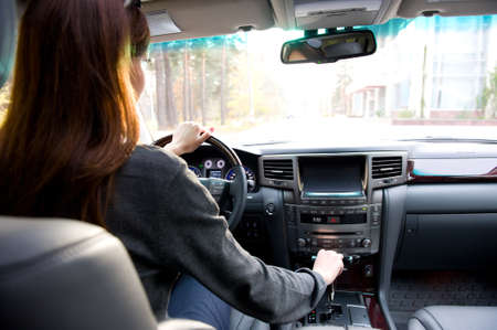 woman driving car: The young woman driving  the car. View from back seats of the car.