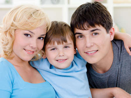 Close-up portrait of happy smiling cheerful family with son - indoors photo