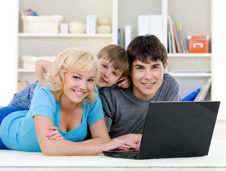 Smiling happy family with son lying together and using laptop at home - indoors photo