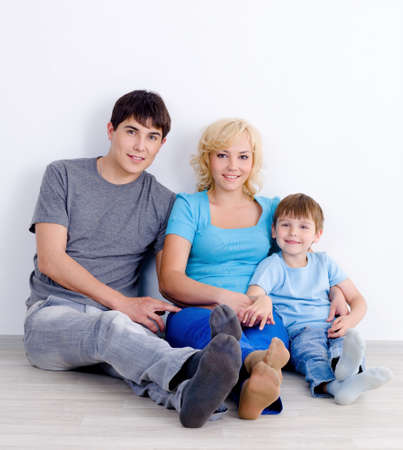 Young family with son sitting together on the floor near the wall with smile - indoors photo