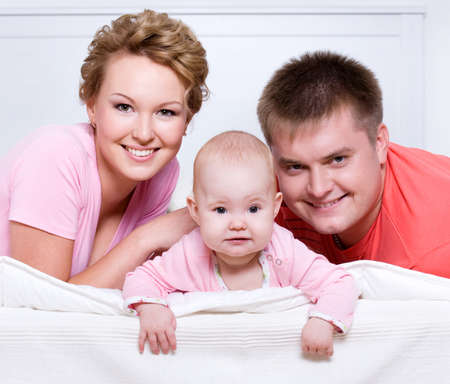 Portrait of the Beautiful young happy family lying in bed at home photo