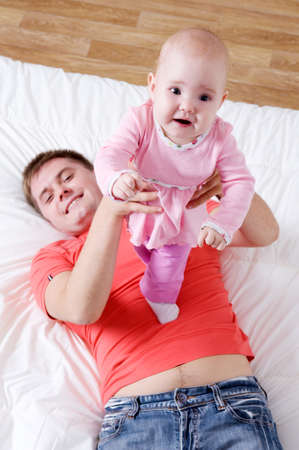Happy young father with smiling baby lying on bed in bedroom - high angle photo