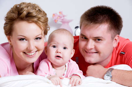 Lifestyle portrait of the Beautiful young happy family lying in bed at home photo