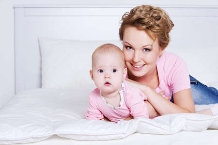 Portrait of happy young beautiful mother lying with her baby on the bed photo