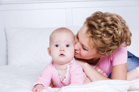 Portrait of young beautiful mather kissing attractive baby lying on bed in the bedroom  photo
