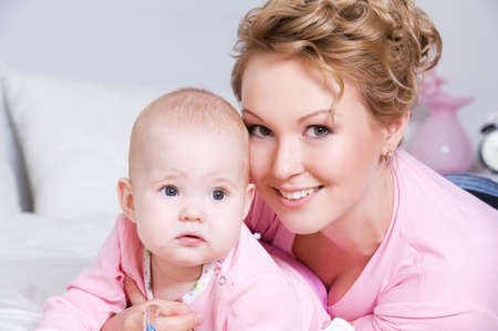 Portrait of happy young attactive mother lying with her baby on the bed at home photo