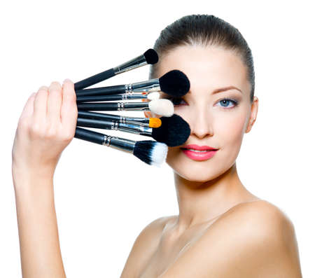 Portrait of the beautiful woman with make-up brushes near\ attractive face. Adult girll posing over white background