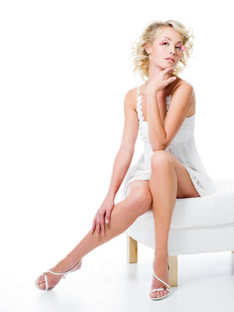 sexy woman with beautiful legs sits on white chair photo