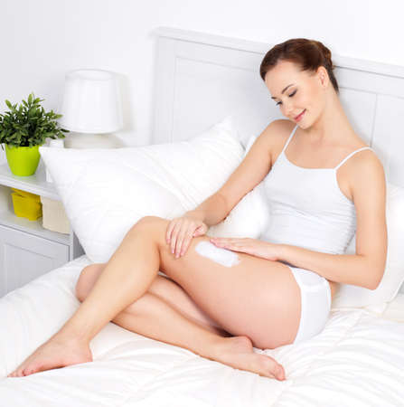 moisturize: Young beautiful woman applying cream for skin on legs - indoors