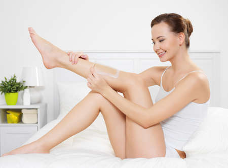 Beautiful young woman depilating skin on legs by waxing is in the bedroom - indoors photo