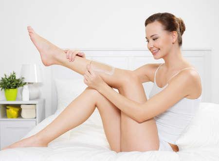 depilacion con cera: Joven y bella mujer depilating de piel en las piernas por depilaci�n es en el dormitorio, en el interior