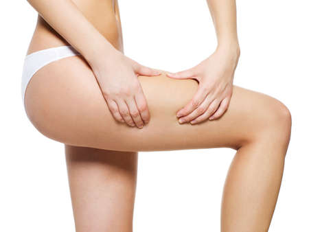 thighs: Female squeezes cellulite skin on her legs - close-up shot on white background