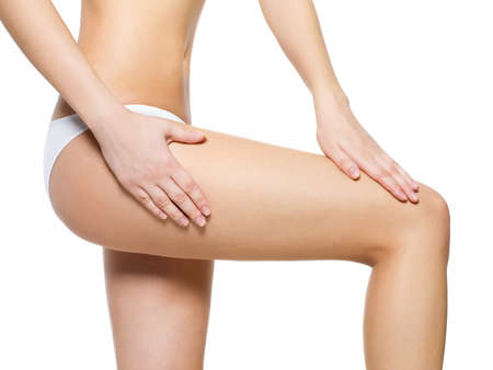hand on hip: Female pampering cellulite skin on her legs - close-up shot on white background