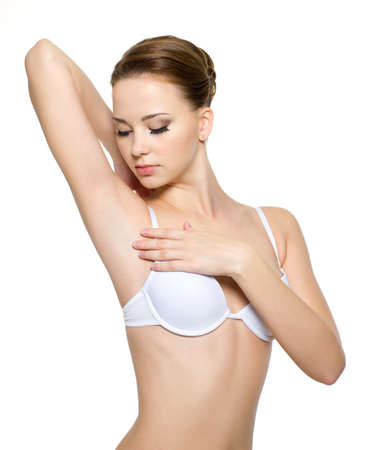 Female touching and looking on her clean armpit - isolated on white photo