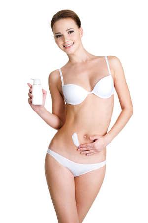 cuerpo femenino: Hermosa mujer feliz aplicar crema cosm�tica en el abdomen de la grasa - posando sobre fondo blanco
