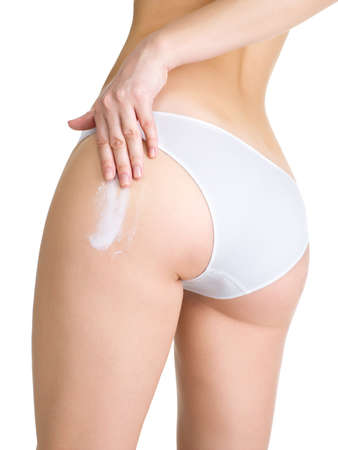 hand on hip: Female applying cosmetic cream from cellulite on leg - isolated onwhite Stock Photo