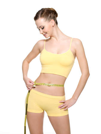 body check: Pretty smiling woman measuring waist with  measurement type isolated on white