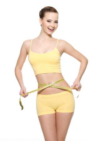 waist: Muy sonriente mujer medir la cintura con tipo de medida aislado en blanco