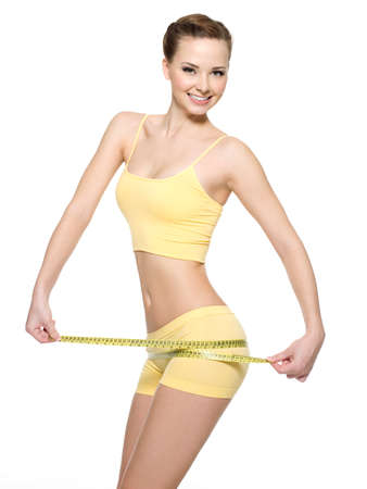 Smiling woman with beautiful body measuring thigh with  measurement type after diet, isolated on white.  photo