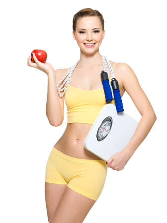 gain: beautiful young woman with perfect sporty body holding scales and apple Stock Photo