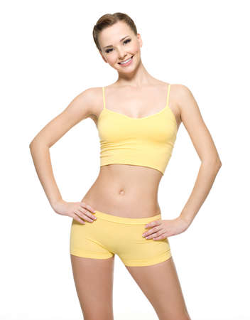 Happy young woman with beautiful slim body in yellow sport clothes -  isolated on white background  Stock Photo - 8416722