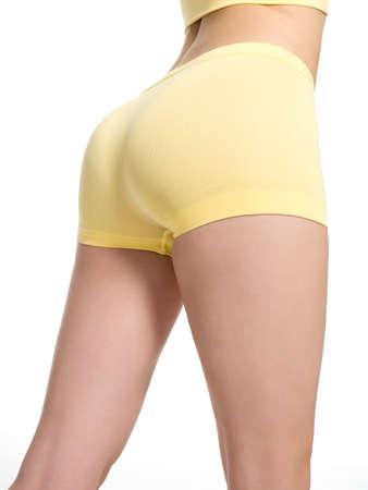 muslos: Mujer joven con hermosas nalgas deportivas y cintura delgada - aislados en blanco Foto de archivo