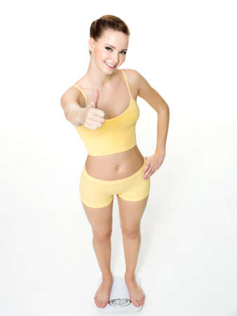 gains: Happy young woman standing on scales and shows the thumbs-up isolated on white. High angle view