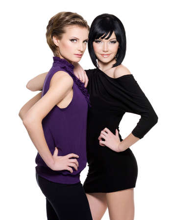 Two beautiful  glamour women standing together over white background photo