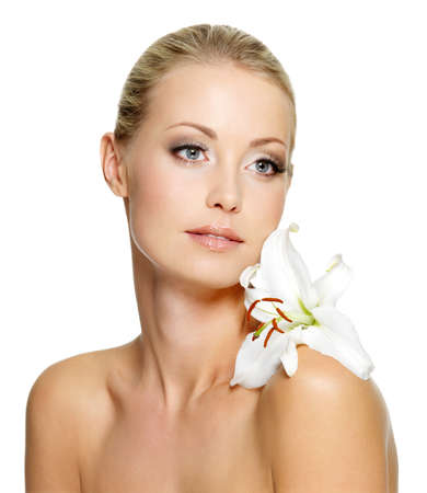 Beauty woman with perfect clean skin and lily flower on shoulder - isolated photo