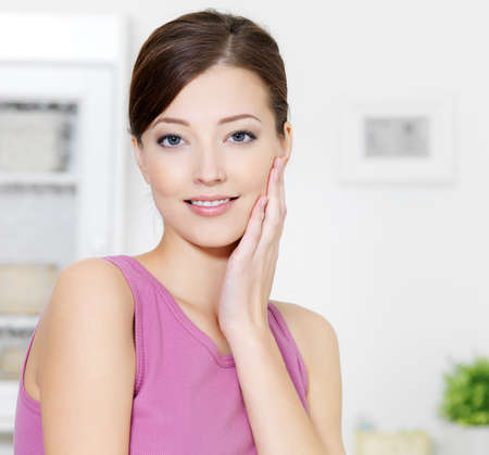 vertical wellness: Woman with clean fresh skin of face looking at camera - indoors