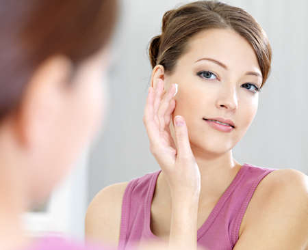 moisturizing: Woman caring of her  beautiful skin on the  face standing near mirror in the bathroom