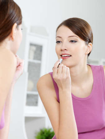 applying lipstick: beautiful  woman paints her lips  with lipstick looking in the mirror at home