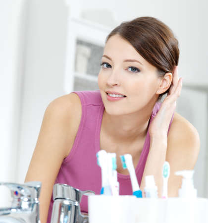 The beautiful smiling woman with clean skin face looking in mirror in a bathroom photo