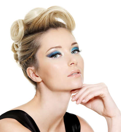 Glamour young woman with blue eye make-up and curly hairstyle on white background photo