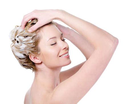 샴푸: Beautiful young blond woman with attractive smile soaping her head - isolated on white background 스톡 사진