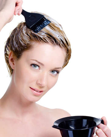 the dying: Portrait of beautiful young blond woman with bowl for hair-dye coloring her head - isolated Stock Photo
