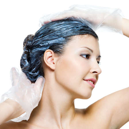dye: Portrait of beautiful young woman dyeing hairs - isolated on white Stock Photo