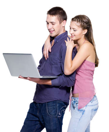 Young beautiful smiling couple looking at laptop - isolated photo