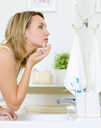 apply: Woman applying  cream on cheek standing in the bathroom and looking at mirror