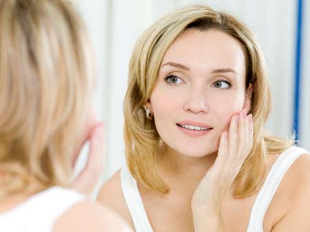 mirar espejo: La hermosa joven con una piel limpia fresca toca con una mano una mejilla
