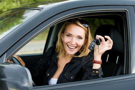 aandrijvingen: Mooie jonge happy vrouw in de nieuwe auto met sleutels - buitenshuis Stockfoto