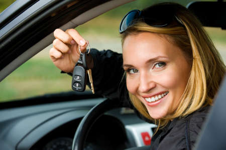 Attractive young happy woman shows keys from the new car - outdoors photo