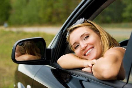 new look: Face of beautiful young happy woman in the new car  - outdoors