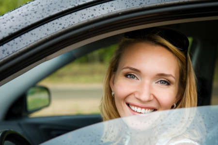 business car: portrait of attractive young cheerful woman in the new car  - outdoors