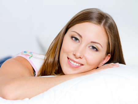 happy beautiful woman lies on a pillow in the bedroom photo