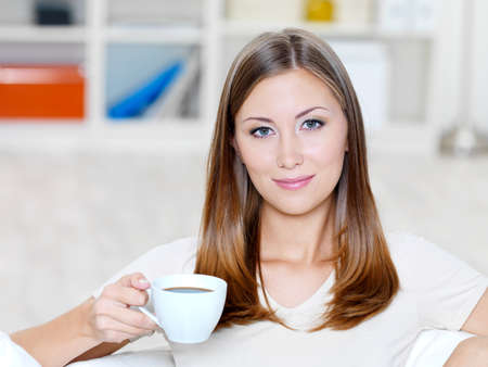 Beautiful smiling young woman with cup of coffee on the sofa - indoors photo
