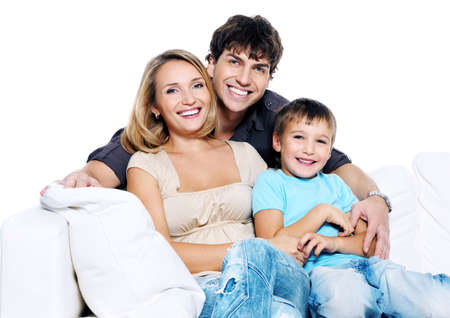 family on couch: Happy young family with child siting on white sofa isolated