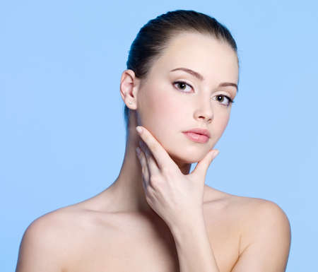 chins: Portrait of young woman with beautiful clean fresh skin on face - blue background Stock Photo