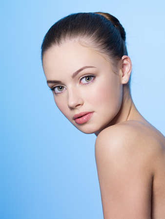 Beautiful young woman with heathy clean skin - blue background photo